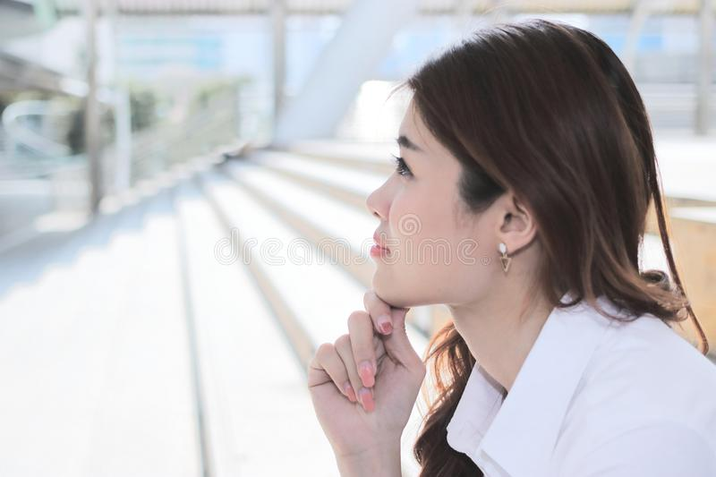 Close up on face of beautiful young Asian woman sitting on stairway and looking at far away with copy space. stock photography