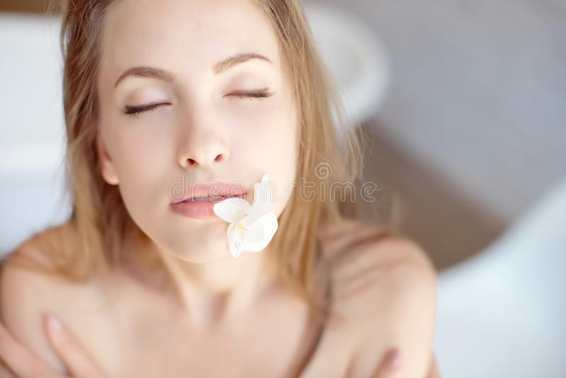 Close-up face of beautiful young woman with health skin and flower in mouth stock images