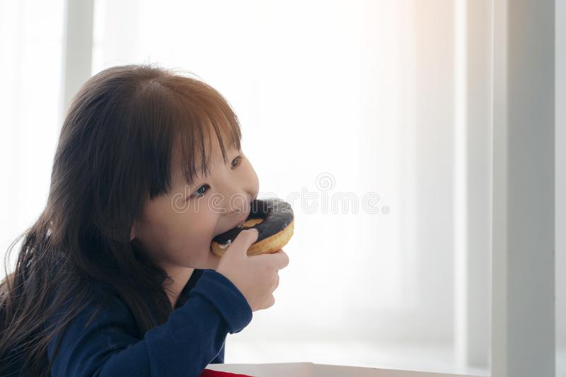 Close up face of hungry little Beautiful Asian girl eating chocolate donut, Cute kid eating donus with yummy face, Child eaitng stock photos
