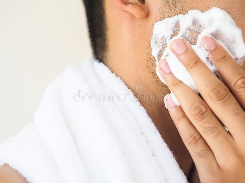 Close up of face of man applying foam on his chin with concentration. Isolated on grey background royalty free stock photo