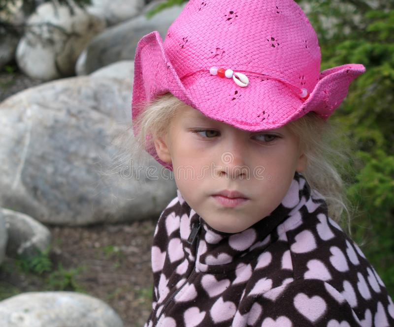 Face pensive little girl in a pink cowboy hat with a seashell. Close-up of a face pensive little girl in a pink cowboy hat with a seashell stock photos
