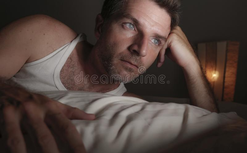 Close up face portrait of attractive sad and thoughtful man lying on bed awake late at night thinking feeling worried and stock photo