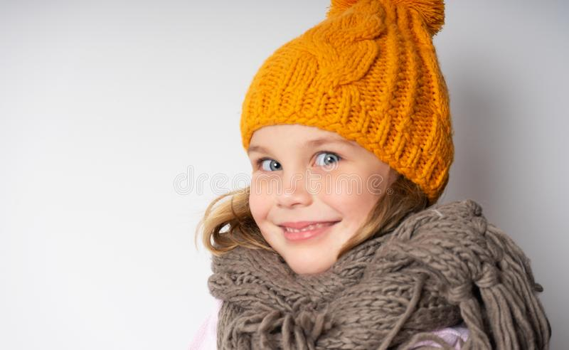 Close up face portrait of toothy smiling young woman wearing knitted hat and scarf. royalty free stock image