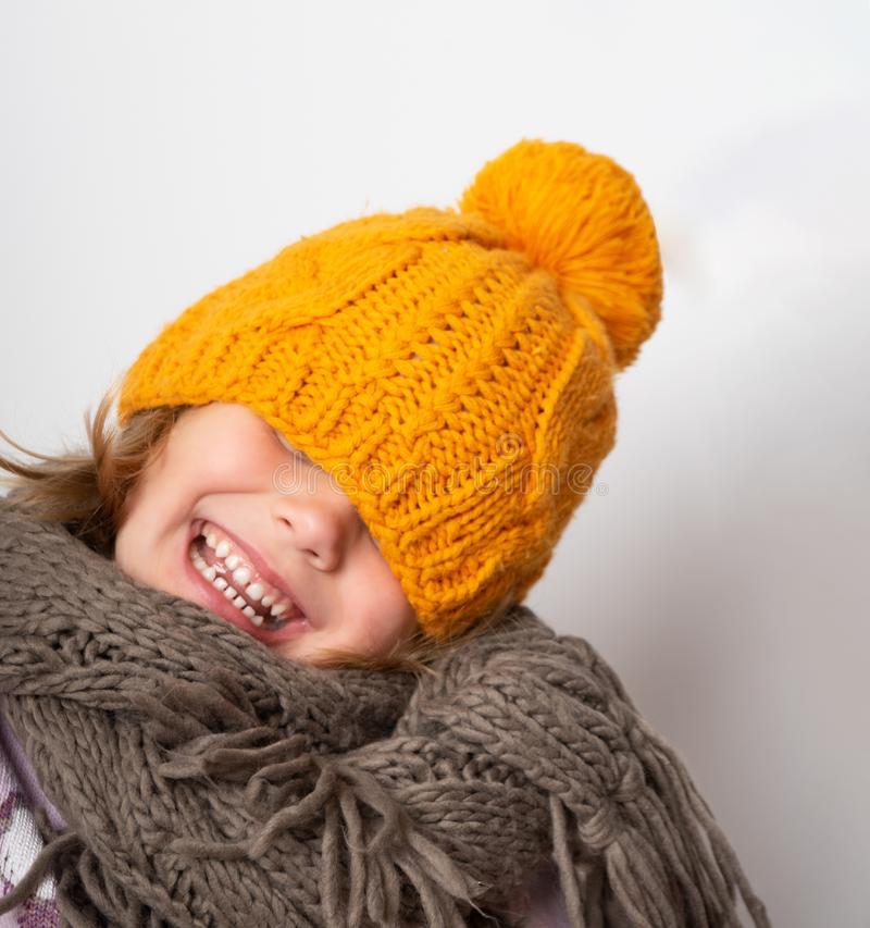 Close up face portrait of toothy smiling young girl wearing knitted hat and scarf. royalty free stock images