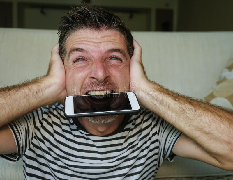 Close up face portrait of young attractive and stressed man biting mobile phone desperate and anxious in crazy frustrated face royalty free stock images