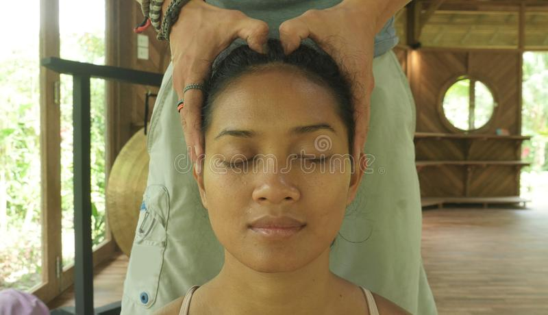 Close up face portrait of young gorgeous and relaxed Asian Indonesian woman receiving traditional facial Thai massage with male stock photo