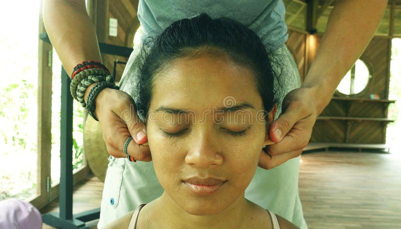 Close up face portrait of young gorgeous and relaxed Asian Indonesian woman receiving traditional facial Thai massage with male stock photography