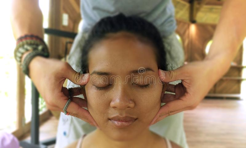 Close up face portrait of young gorgeous and relaxed Asian Indonesian woman receiving traditional facial Thai massage with male royalty free stock photography