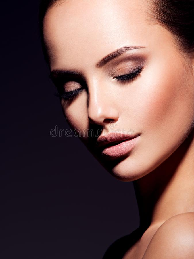 Close-up face of a pretty  girl with brown make-up of  eyes. Closeup portrait of a beautiful  fashion woman with glamour makeup posing at studio isolated on stock image