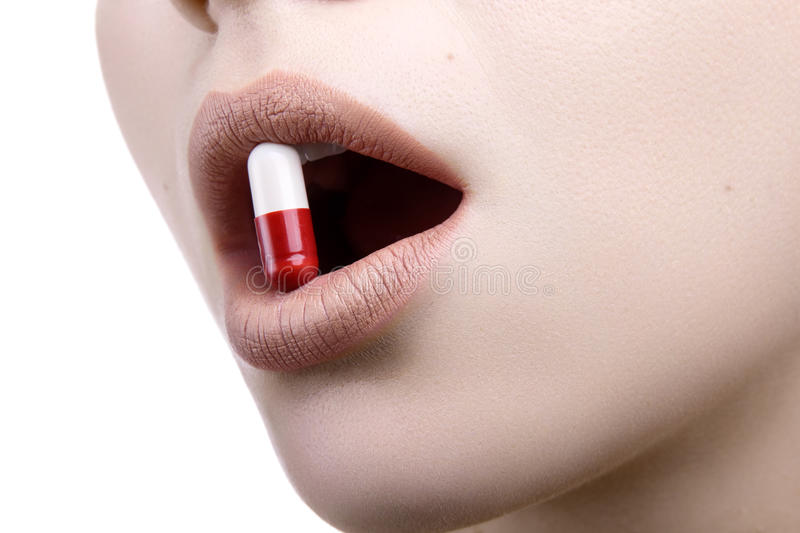Close up of a face with the red white pill medicine in her mouth stock photography