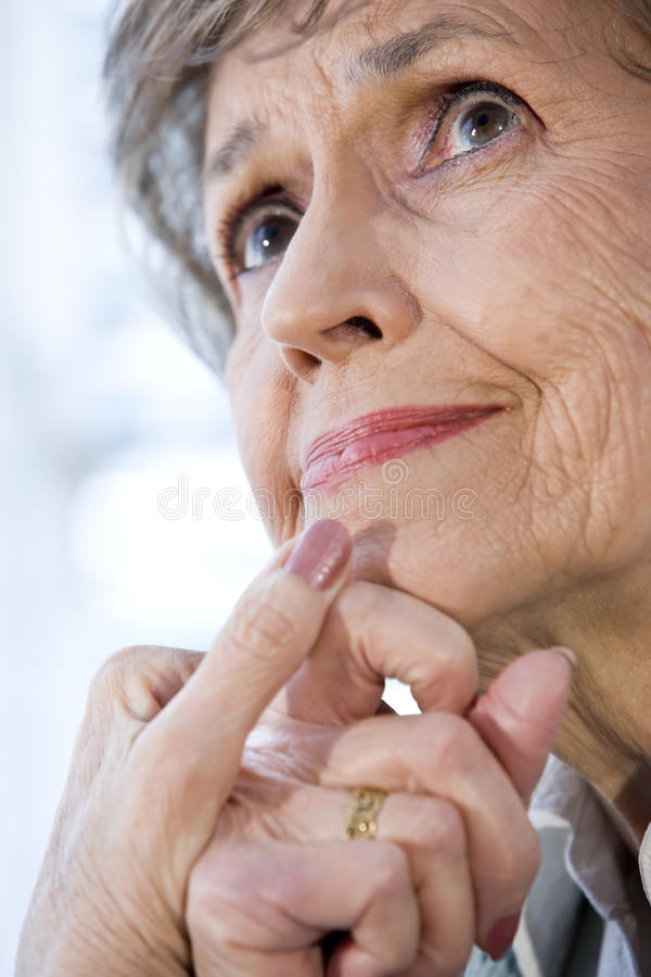 Close up face of senior woman thinking. Hands on chin royalty free stock photos