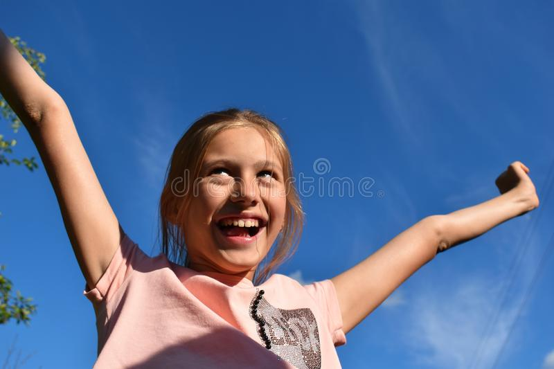 Beautiful little girl on background of clear blue sky in the summer stock photography