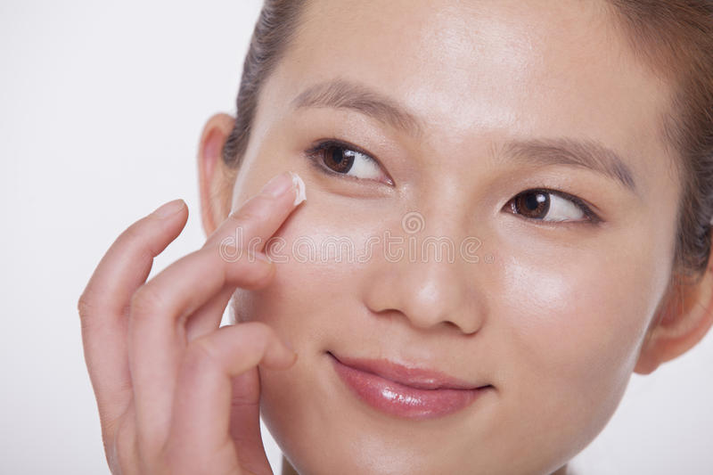 Close up on the face of a smiling young woman applying cream to her face, studio shot stock photo