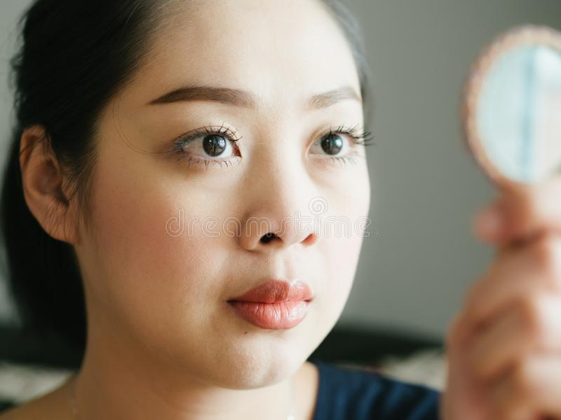Close up face of woman in normal emotion with low light from win. Close up face of Asian woman in normal emotion with low light from window stock images
