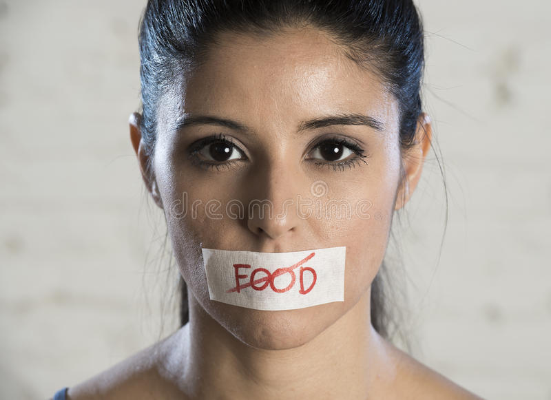 Close up face of young beautiful sad latin woman with mouth sealed on stick tape with the text no food stock image