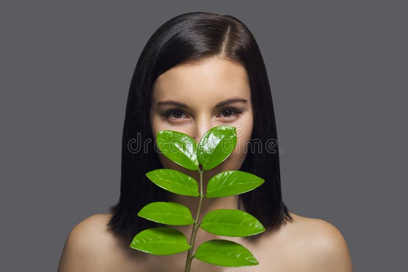 Close-up face of young beautiful woman with green leaf. Beauty portrait of brunette with perfect health skin and hair, natural stock photo