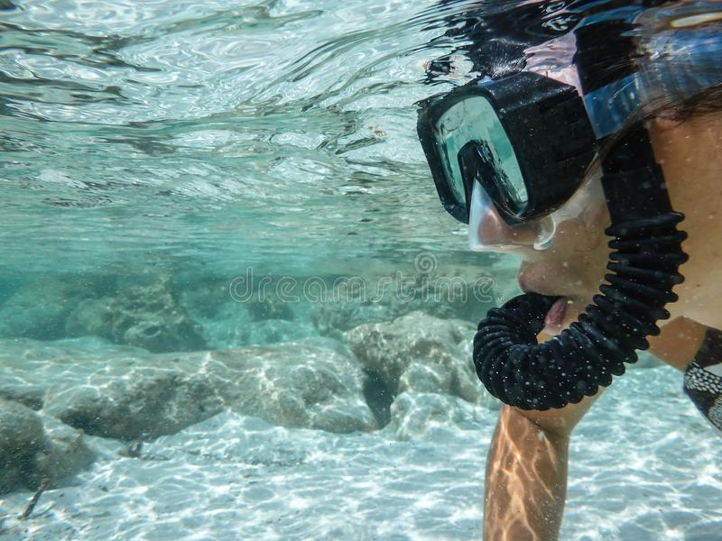 Close up of the face of a young woman in bikini with mask and snorkel shooting underwater in the crystal clear sea with white sand royalty free stock photos