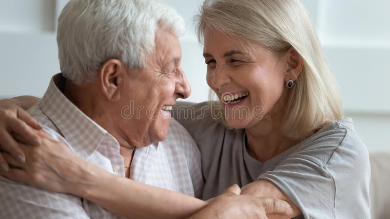 Close up faces elderly wife and senior husband embracing indoors. Close up faces elderly 50s wife and old 70s husband embracing indoors, couple looking at each stock photos