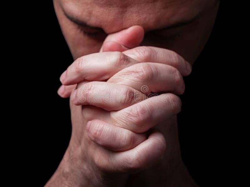 Close up of faithful mature man praying, hands folded in worship to god stock photo