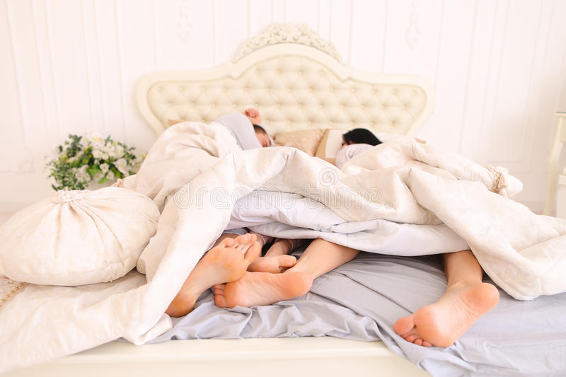 Close-up family feet that lie and sleep on bed. Husband, wife and daughter sleep in bed. Taking Close-up family feet to embrace. Mom, Dad European appearance stock photo