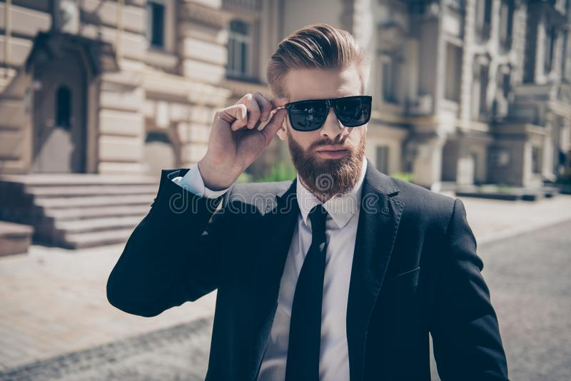 Close up of a famous guy in formal wear and sunglasses outdoors. royalty free stock photos