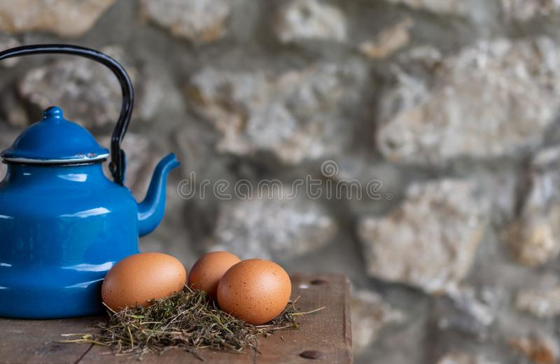 Close-up of farm eggs on hay, with zinc coffee maker on wooden table royalty free stock image