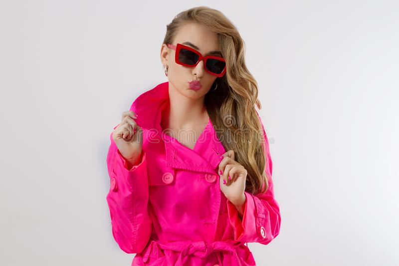 Close up fashion girl in pink clothes and red sunglasses  on white background with copy space. Colorful wardrobe. And glamour beauty concept. Woman fashion and royalty free stock photography