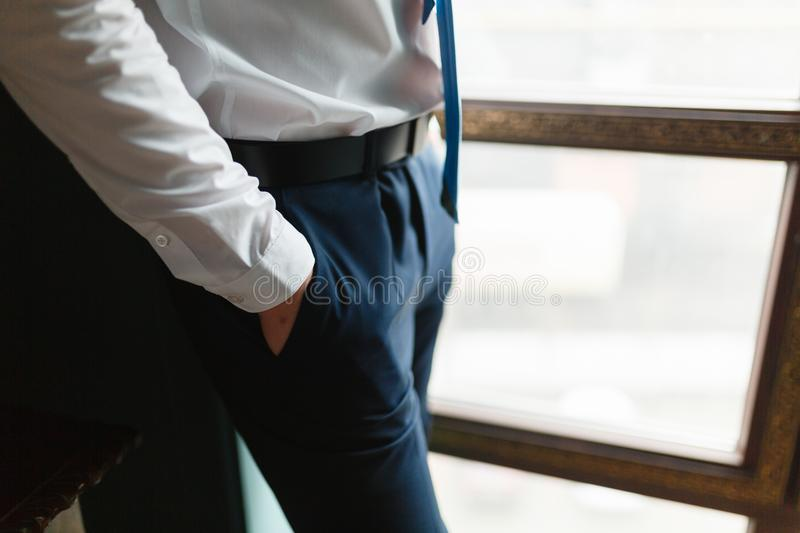 Close up fashion image of the wrist in the pants of many. Detail the body of a businessman. Men's hand in a white shirt, dark blu royalty free stock image
