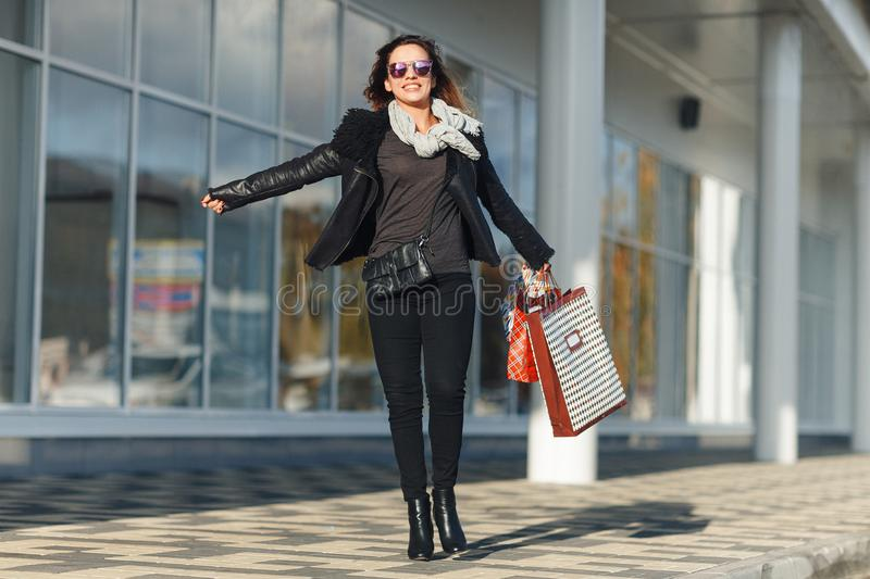 Close up fashion lifestyle portrait young hipster girl, with shopping bags walking out from shop. stock images