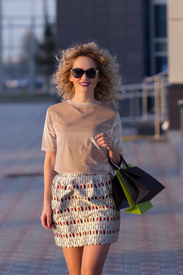 Close up fashion lifestyle portrait young hipster girl, with shopping bags walking out from shop stock image