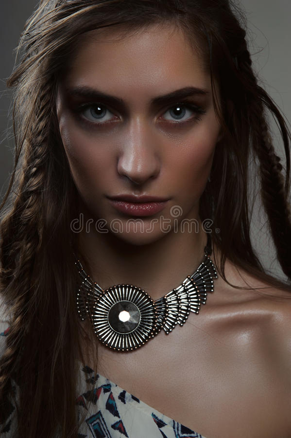 Close-up fashion portrait of brunette with big eyes and pendant. Close-up fashion portrait of brunette horsewoman with braids, big eyes and pendant stock photo