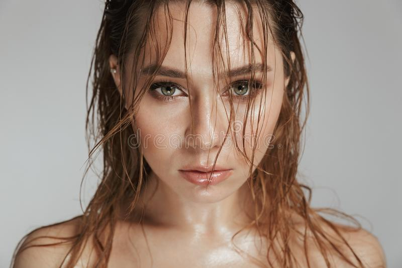 Close up fashion portrait of a topless sensual woman. With makeup and wet hair posing isolated over gray background stock images