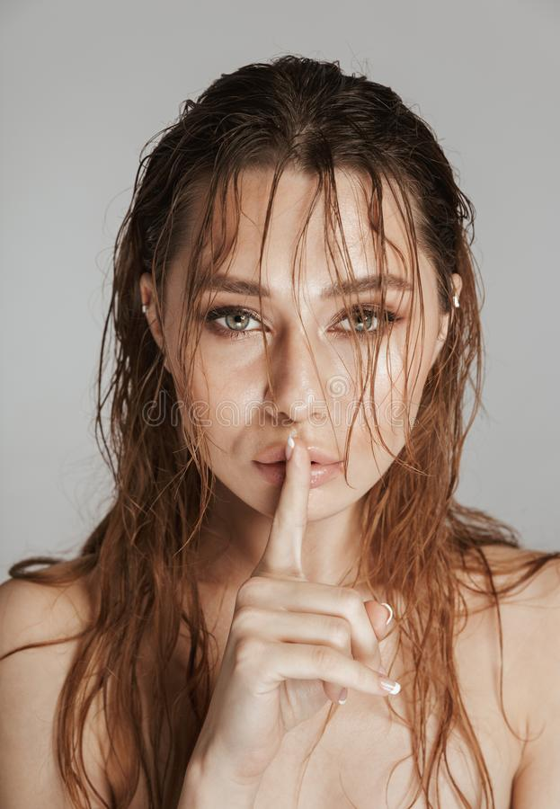 Close up fashion portrait of a topless young woman. With makeup and wet hair showing silence gesture isolated over gray background stock photos