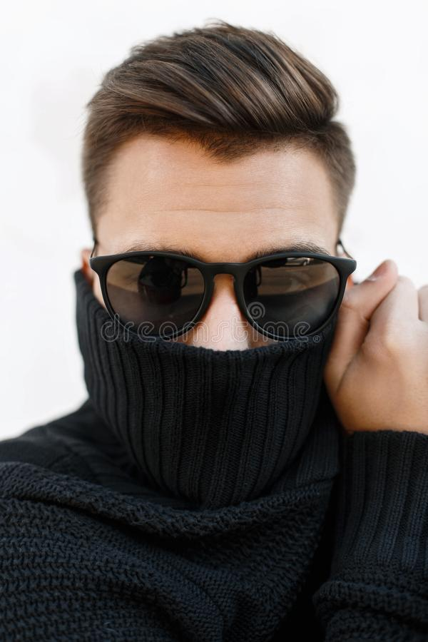 Close-up fashion portrait of a young handsome guy with stylish h. Airstyle in sunglasses and knitted sweater. Covers face with a cloth stock photos