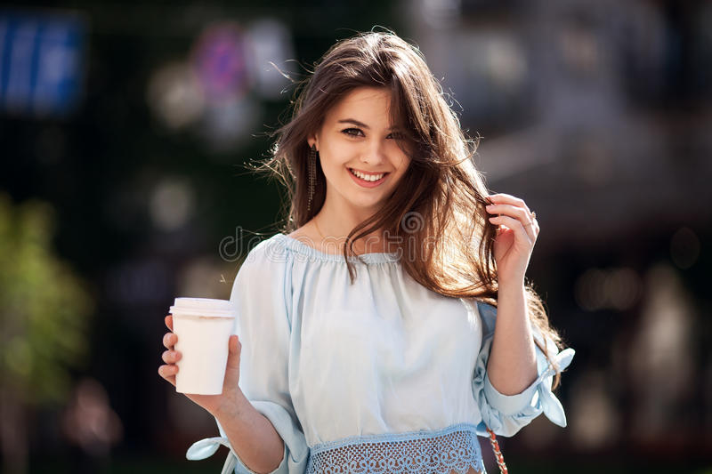 Close up fashion street style portrait of a beautiful girl in a casual outfit walks in the city . Beautiful brunette Keeps coffee. Close up fashion street style royalty free stock photo