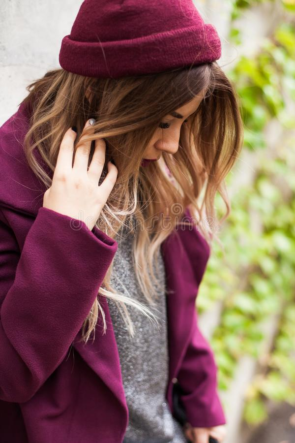 Close-up of a fashionable girl in a red knitted hat and a purple autumn coat. A woman hides her face, looks down stock photo