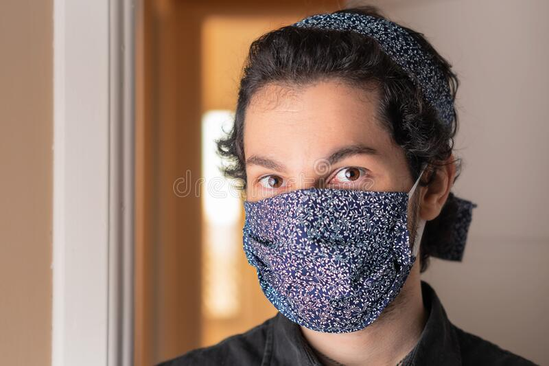 Close up of fashionable man with mask and head bandlooking at camera. In front of apartment door. Individuality, style, identity, royalty free stock photos