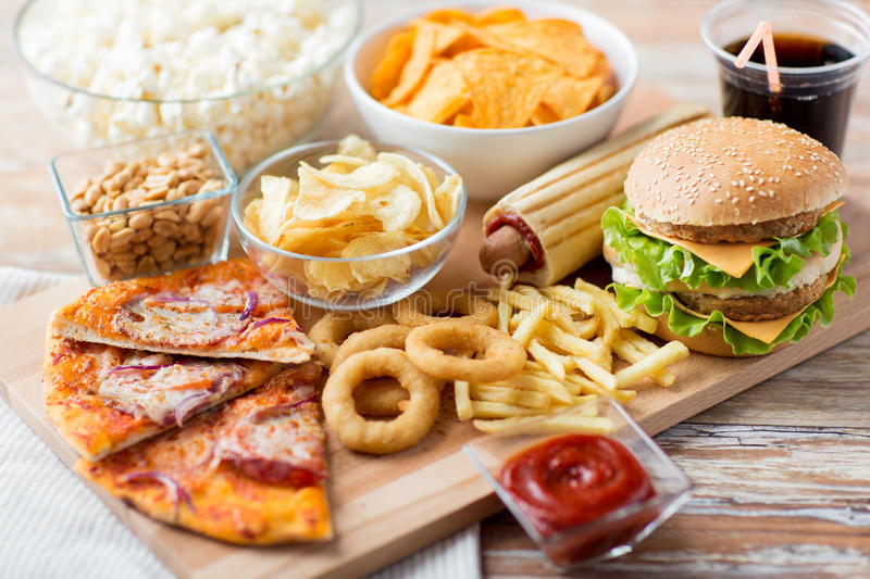 Close up of fast food snacks and drink on table royalty free stock photography