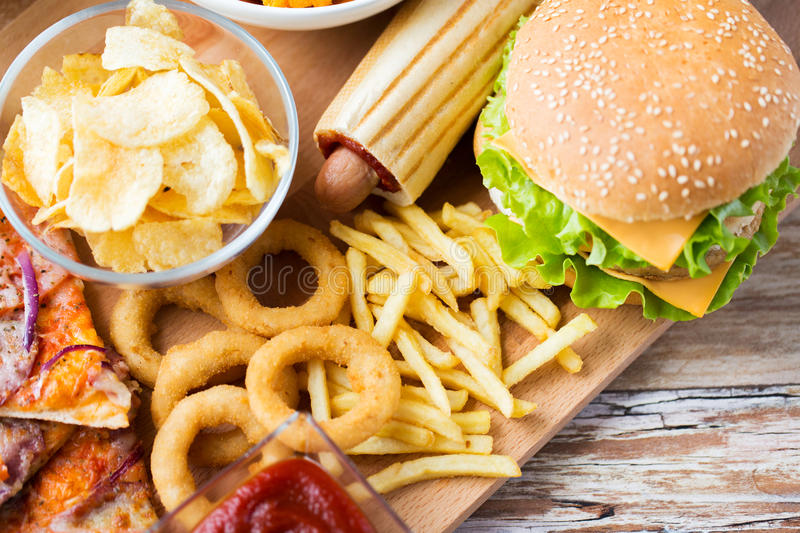 Close up of fast food snacks on wooden table royalty free stock photos