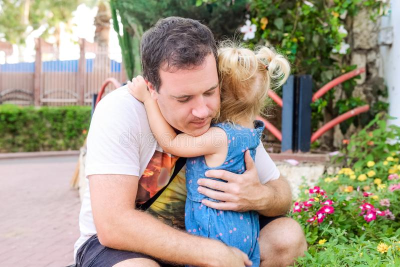 Close up father calm and embracing his little toddler daughter outdor in the park. Family relations. Parenthood care. Selective fo stock photography