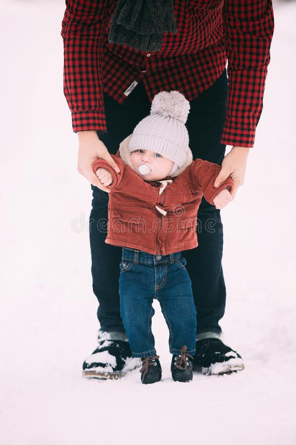 Close up.the father helps his son to take the first steps in snowy winter forest royalty free stock photos