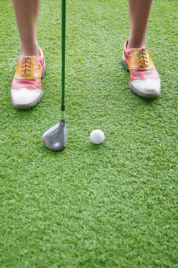 Close up on feet and golf club getting ready to hit a golf ball stock photography