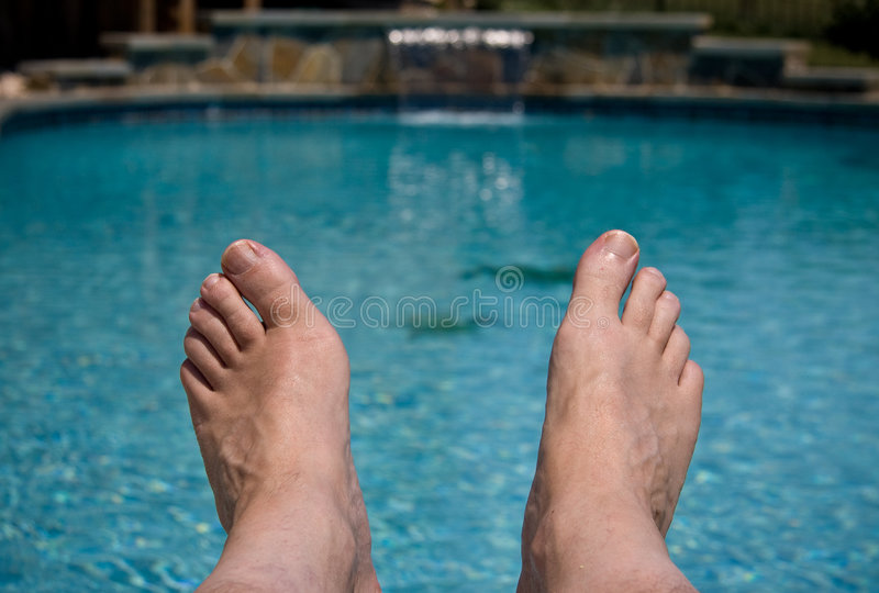 Download Close up of feet over pool stock image. Image of resort - 5594303