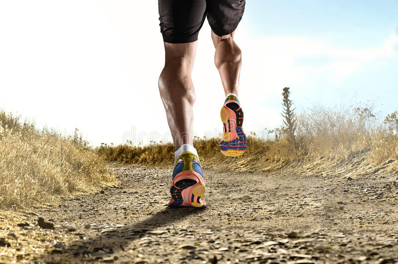 Close up feet with running shoes and strong athletic legs of sport man jogging in fitness training workout royalty free stock photo