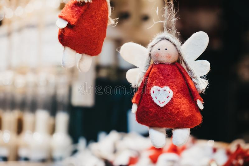 Felt red and white angel Christmas tree decorations on sale at a Christmas Market. Close up of felt red and white angel Christmas tree decorations on sale at a stock images