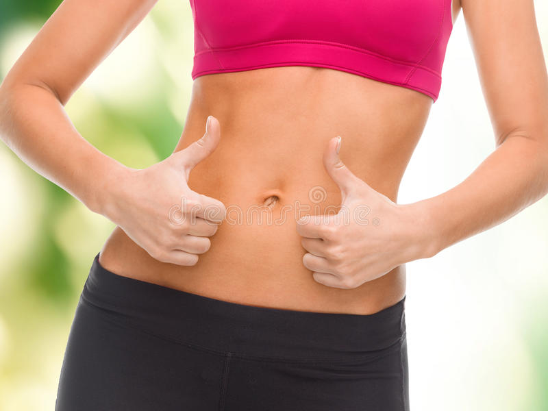 Close up of female abs and hands showing thumbs up. Fitness and diet concept - close up of female abs and hands showing thumbs up royalty free stock photo