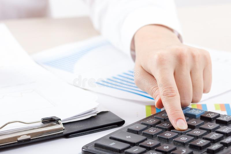 Close up of female accountant or banker making calculations. Savings, finances and economy concept stock photography
