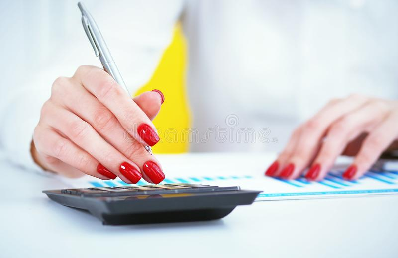 Close up of female accountant or banker hand making calculations. Savings, finances and economy concept royalty free stock photos