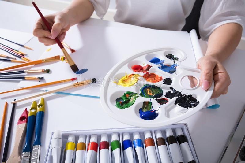 Artist Holding Paint Palette While Painting On Canvas Paper. Close-up Of An Female Artist`s Hand Holding Paint Palette While Painting On Canvas Paper royalty free stock photo