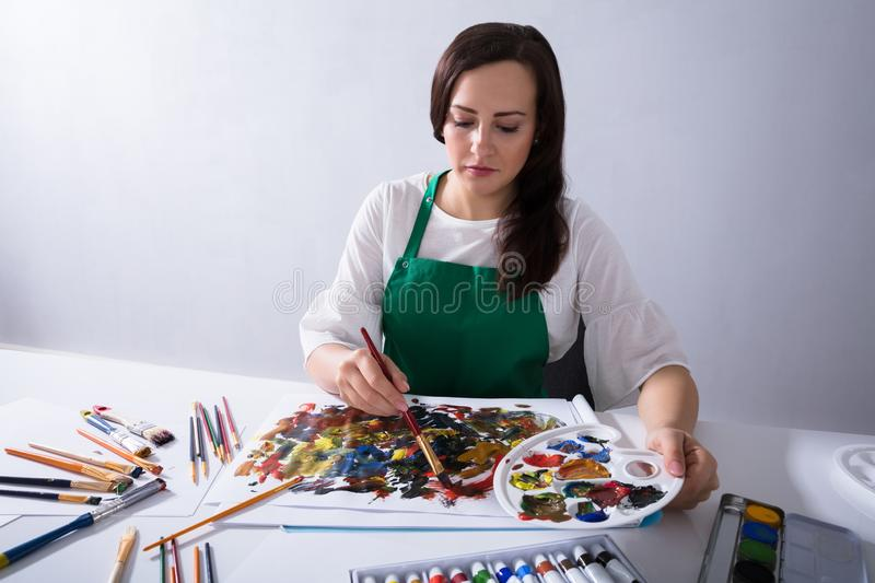 Artist Holding Paint Palette While Painting On Canvas Paper. Close-up Of An Female Artist`s Hand Holding Paint Palette While Painting On Canvas Paper stock photo